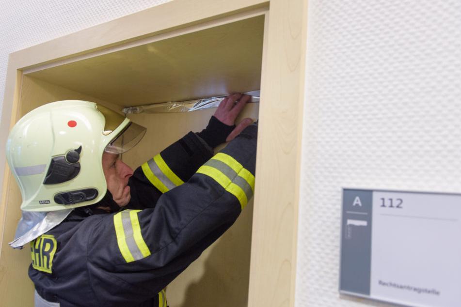 Ein Feuerwehrmann versiegelt eine Tür im Gericht.
