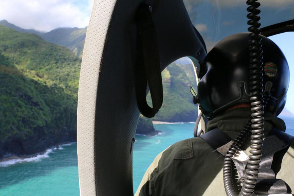 Das vom Hawaii Department of Land and Natural Resources zur Verfügung gestellte Foto zeigt ein Such- und Rettungsteam der Küstenwache, das über dem Napali Coast State Wilderness Park, auf Kauai, nach einem vermissten Ausflugshubschrauber sucht.