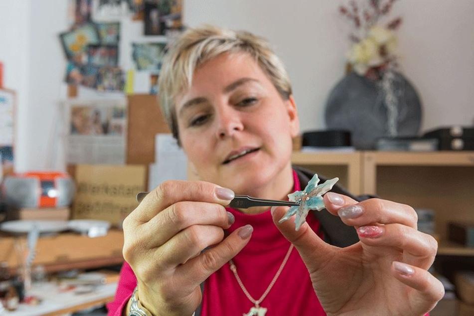 Die gelernte Porzellan-Malerin setzt einen funkelnden Kristall auf einen ihrer zarten Schmuck-Sterne.
