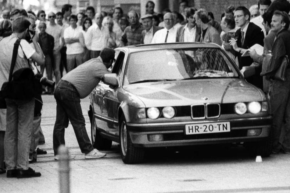 Der Wagen mit den Geiselnehmern wird in Köln von Journalisten umringt.