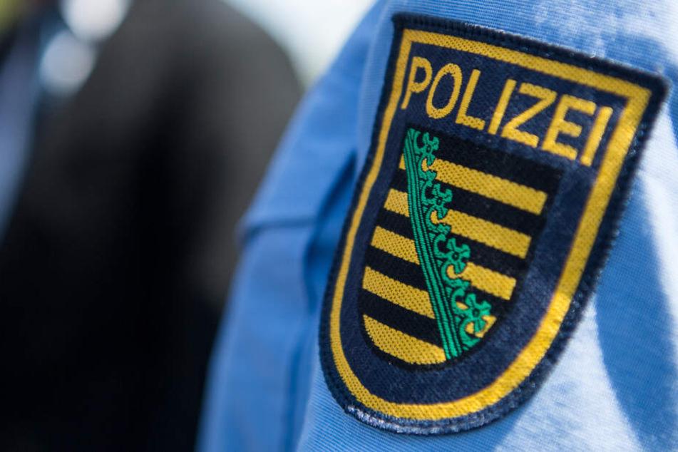 Logo der sächsischen Polizei ist an einem Polizeiuniform angebracht.