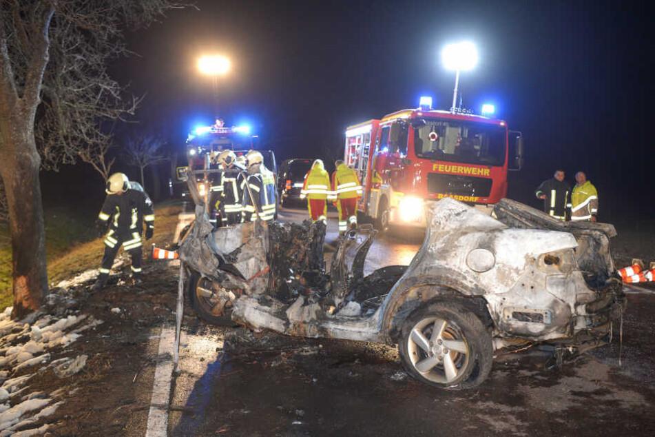 Feuerwehrleute und Rettungskräfte stehen auf einer Landstraße hinter dem ausgebrannten Auto.