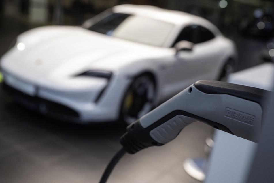 Ein elektrischer Porsche Taycan Turbo S steht im Porsche Zentrum Stuttgart hinter einer angedeuteten Ladesäule. Der Sportwagenbauer will zusammen mit einem Partner im kleinen Umfang Hochleistungs-Batteriezellen herstellen.