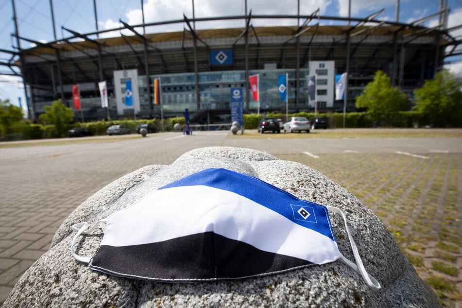 Eine Mund-Nasen-Schutzmasken in den Farben des Hamburger SV liegt auf einem steinernen Fußball auf dem Parkplatz vor dem Volkspark Stadion.
