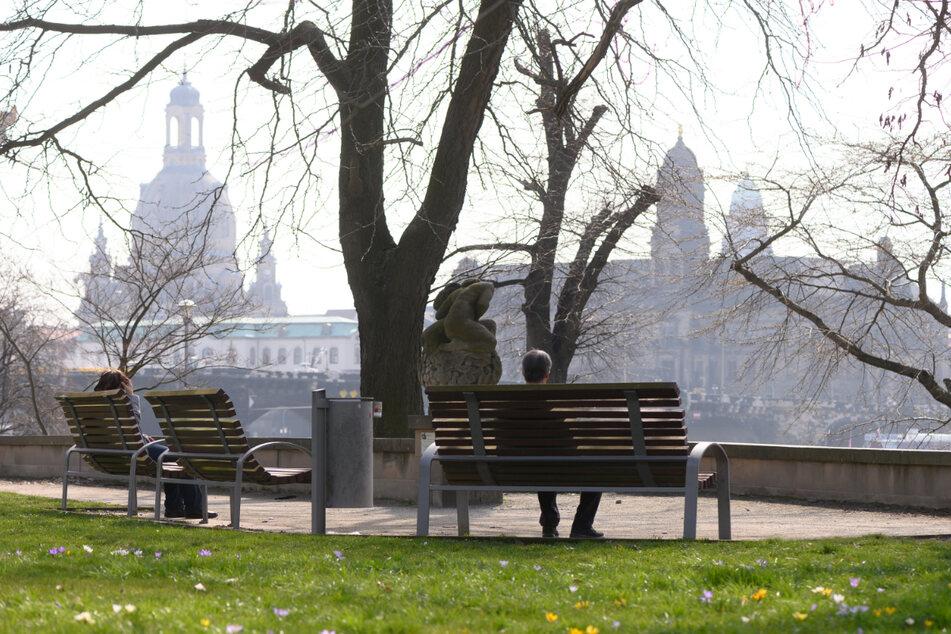 Passanten sitzen am Ufer der Elbe vor der Kulisse der Altstadt mit der Frauenkirche (l.) und dem Ständehaus auf einer Bank.