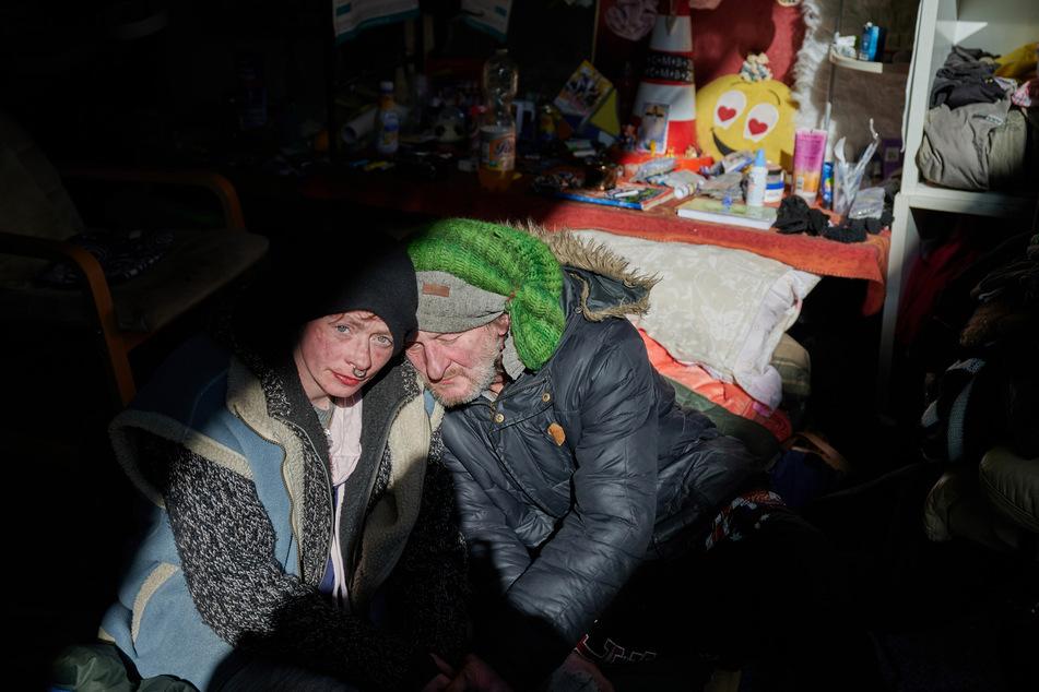 Gogo sitzt mit seiner Freundin Elli an seiner Schlafstelle unter einer Eisenbahnbrücke in Bochum, die sie sich mit Fundstücken wohnlich gestaltet haben.