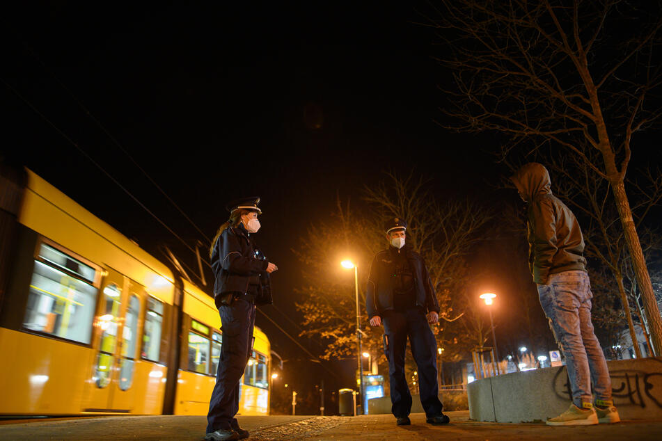 Polizisten überprüfen in der Nacht im Rahmen einer Kontrolle der Ausgangssperre einen Mann an einer Haltestelle. An einigen Orten in NRW dürfen die Menschen nachts nur noch aus wichtigen Gründen vor die Tür (Symbolbild).
