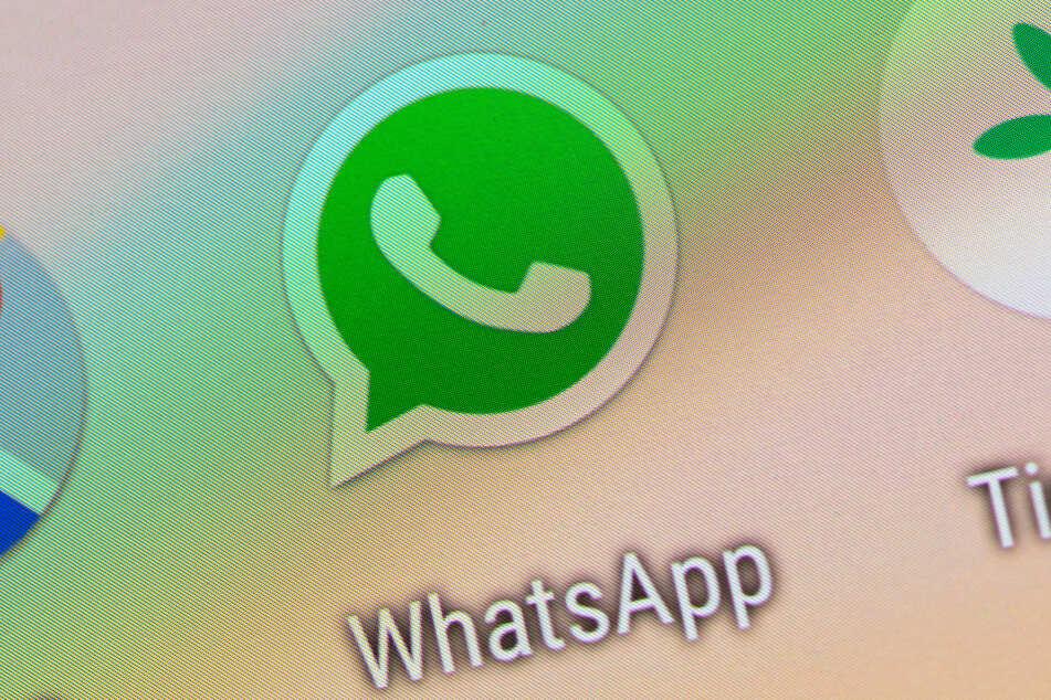 Das Logo der Messenger-App WhatsApp ist auf dem Display eines Smartphones zu sehen.