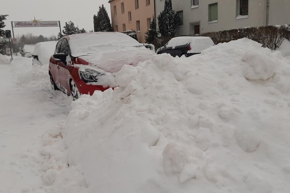 Riesige Schneeberge blockieren ein Auto in Leipzig-Holzhausen.