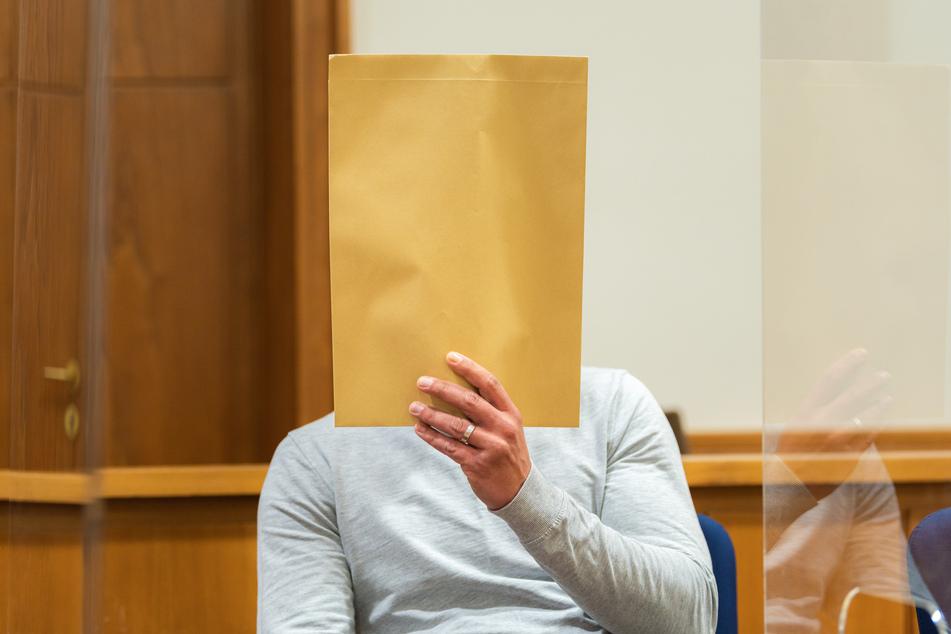 Der 33-Jährige sitzt mit einem Umschlag vor dem Gesicht in einem Gerichtssaal des Landgerichts Oldenburg.