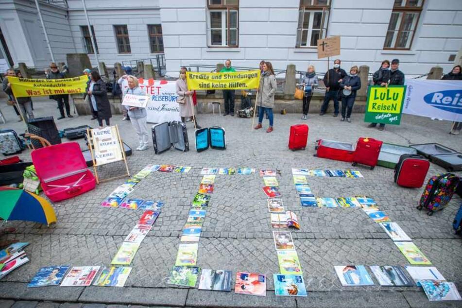 """Mit Reisekatalogen haben Besitzer und Mitarbeiter aus Reisebüros bei einer Protestaktion vor der Staatskanzlei den Schriftzug """"SOS"""" gelegt."""