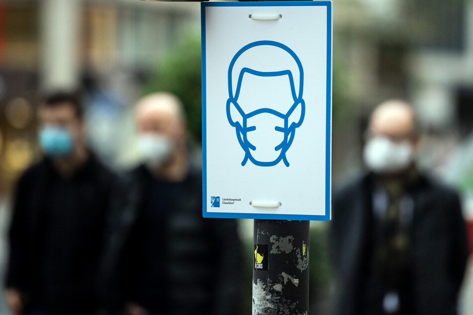 Menschen mit einer Corona-Maske: In Düsseldorf musste ein Mafia-Prozess wegen Corona-Infektionen unterbrochen werden. (Symbolbild)