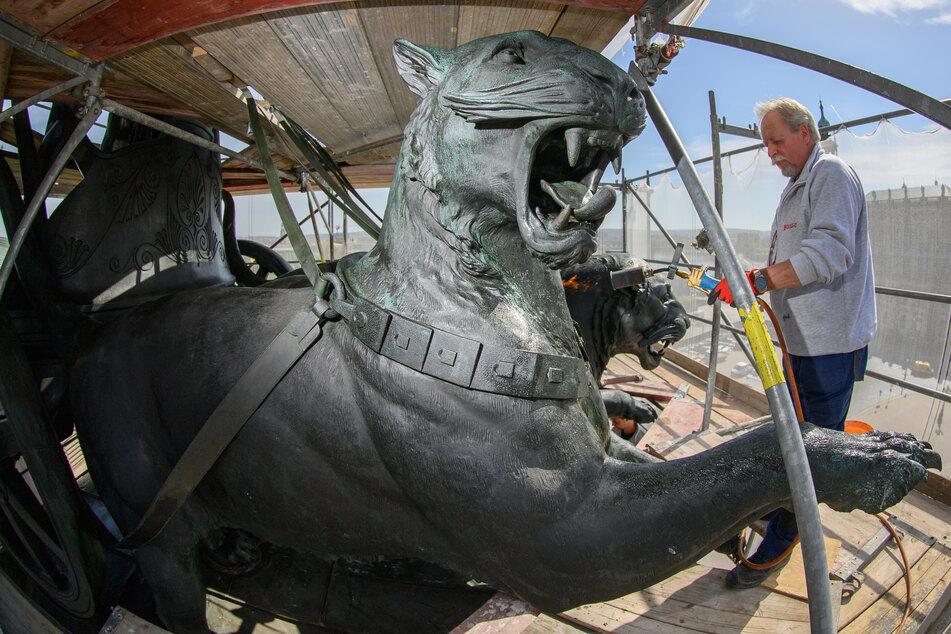 Andreas Kunze, Metallrestaurator der Firma Fuchs und Girke, bearbeitet die Panther der Quadriga auf der Semperoper mit Heißwachs.