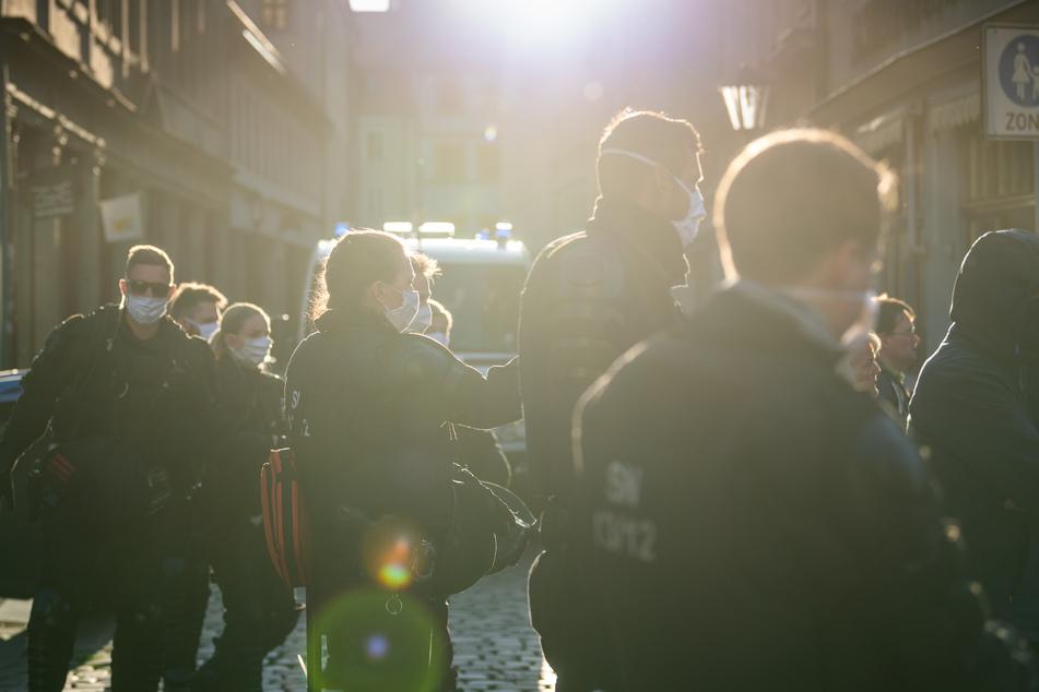 Polizisten stehen in Pirna am Rand einer Demonstration von Gegnern der Corona-Maßnahmen auf dem Marktplatz in einer Seitenstraße.