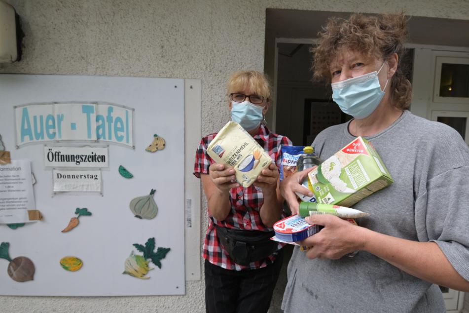 Kathrin Barth (54, l.) und Silvia Rudolf (60) von der Auer Tafel packen Lebensmittel von den Johannitern in Care-Pakete für Hilfsbedürftige.