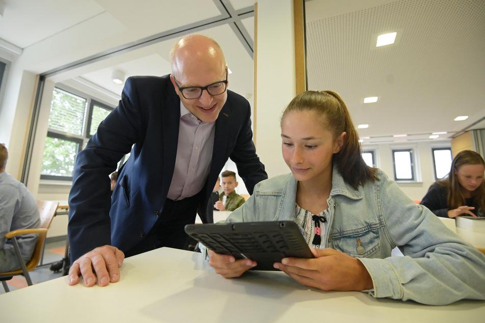 Bürgermeister Sven Schulze (48, SPD) betrachtet mit Sportgymnasium-Schülerin Nelly (13) eines der neuen Tablets.