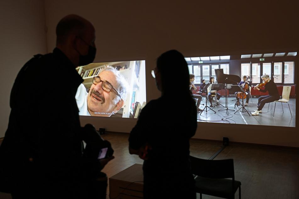 Ausstellungsbesucher stehen vor Boaz Kaizmans Videoinstallation über das jüdische Leben in Deutschland.
