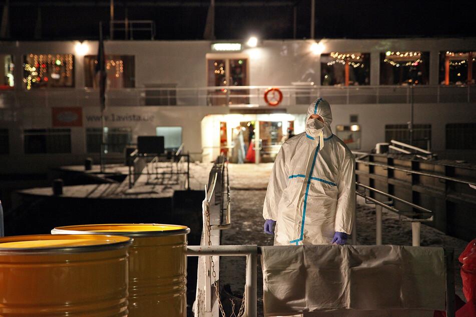 Ein Rettungssanitäter im Schutzanzug steht vor einem Hotelschiff. (Archivbild)