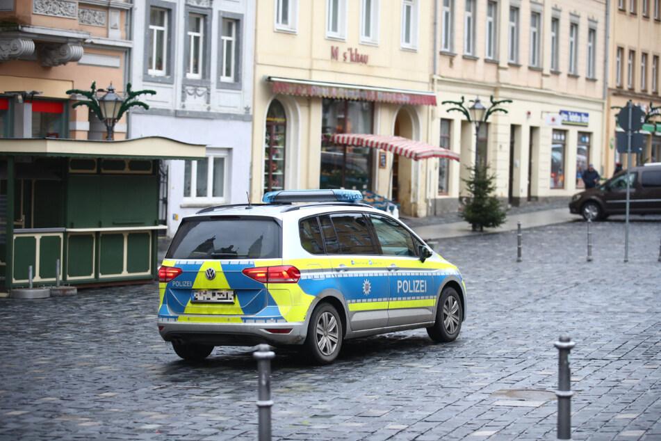 Ein Polizeifahrzeug fährt über den fast Menschenleeren Marktplatz im Zentrum der Stadt Altenburg. Mit einem Bewegungsradius von 15 Kilometern sollen die Infektionszahlen gesenkt werden.