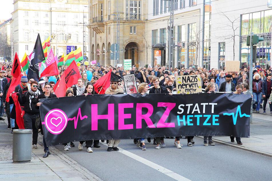 """Demonstranten laufen mit einem """"Herz statt Hetze""""-Banner über die Wilsdruffer Straße."""