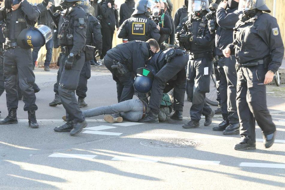 Ein Demonstrant wird von Polizisten zu Boden gerungen.