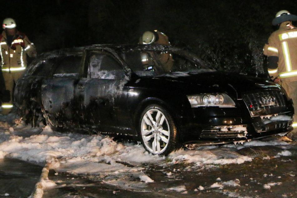 Feuerwehrleute begutachten den ausgebrannten Audi.