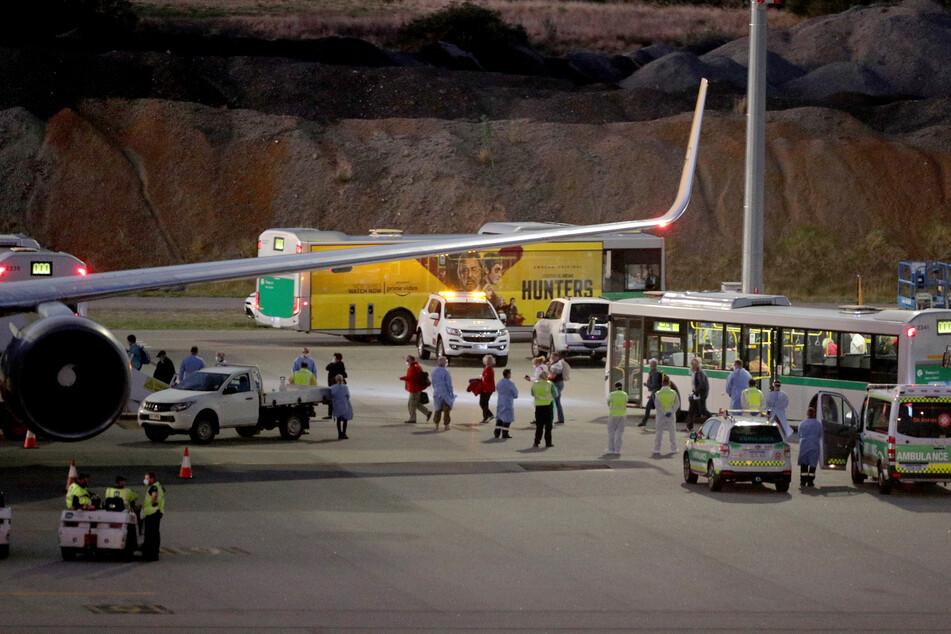 """Passagiere des deutschen Kreuzfahrtschiffes """"MS Artania"""" gehen auf dem Flughafen Perth International von Bussen über das Rollfeld zu einem Flugzeug der Condor Airlines, das sie zurück nach Deutschland gebracht hat."""