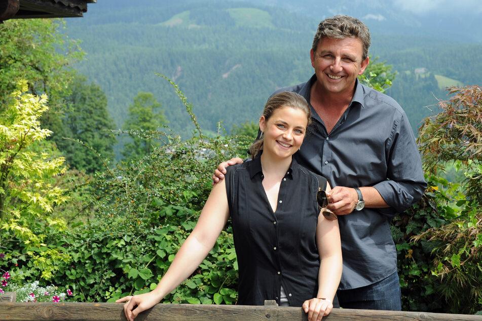 """Die Schauspieler Hans Sigl (als Dr. Martin Gruber) und Ronja Forcher (als seine Filmtochter Lilli Gruber) posieren bei Dreharbeiten der ZDF-Serie """"Der Bergdoktor"""". (Archiv)"""