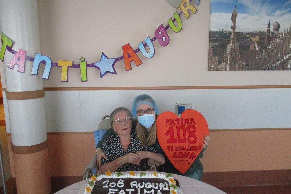 """Fatima Negrini, eine 108-jährige Frau aus Norditalien, sitzt in einem Rollstuhl vor einer Geburtstagstorte, neben ihr steht eine Pflegekraft mit einer riesigen herzförmigen Geburtstagskarte mit der Aufschrift """"Fatima 108 Wir lieben dich !!! S. Faustino""""."""