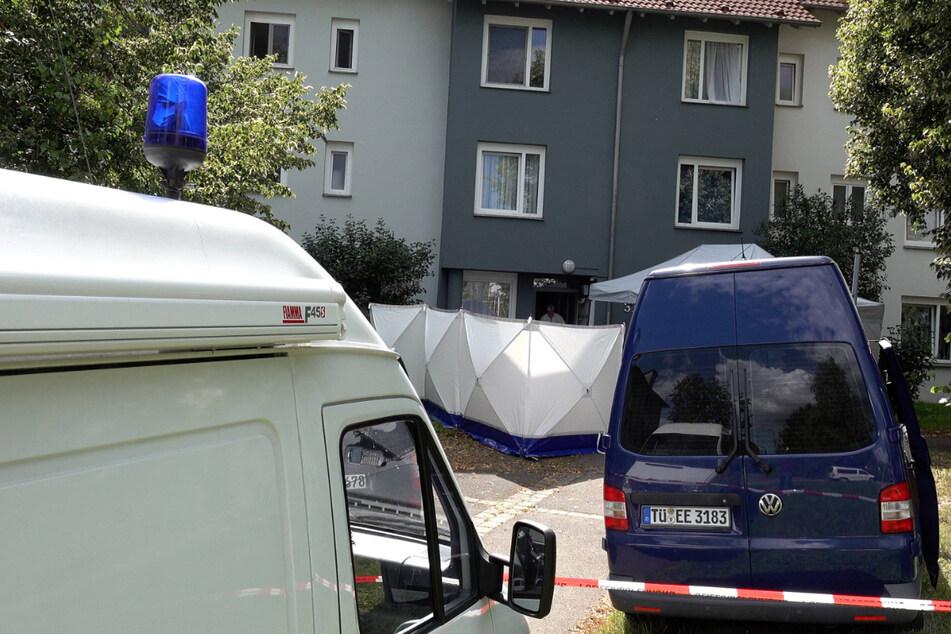 Einsatzfahrzeuge der Polizei stehen vor einer Wohnung in Reutlingen, in der mehrere tote Menschen gefunden wurden.