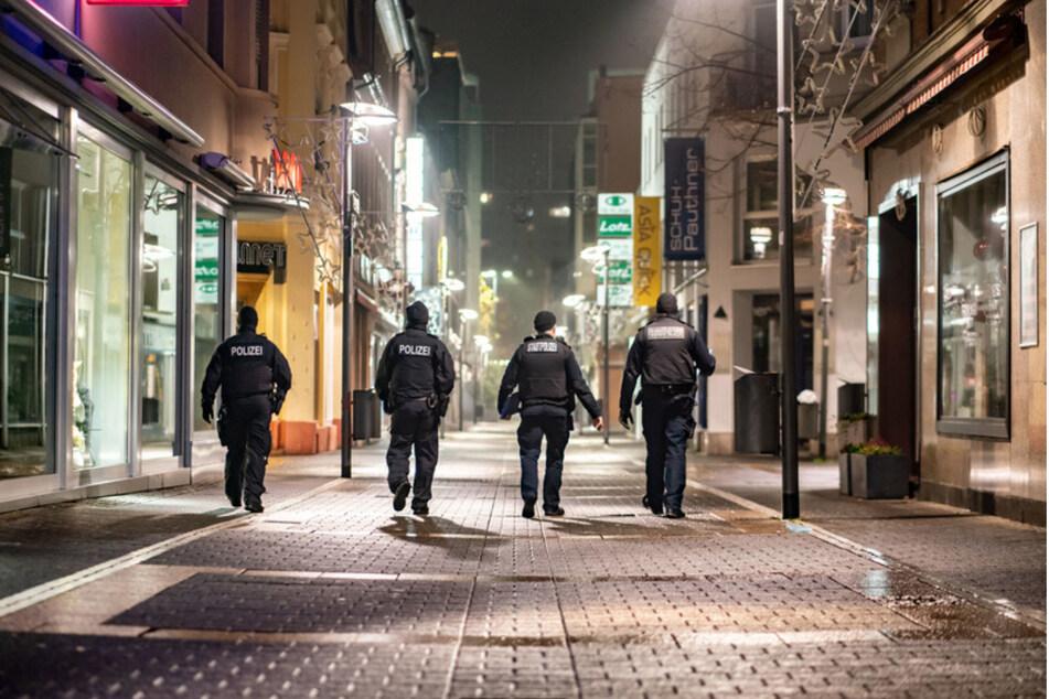 Eine Streife aus jeweils zwei Beamten der Stadtpolizei und der Bundespolizei geht in der nächtlichen Innenstadt, um die Einhaltung der erstmals verhängten nächtlichen Ausgangsbeschränkungen aufgrund hoher Corona-Zahlen zu überwachen.