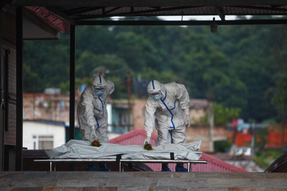 Gesundheitshelfer der nepalesischen Armee, die Schutzanzüge tragen, legen in einem Krematorium Blumen auf den Körper eines verstorbenen Covid-19-Patienten.