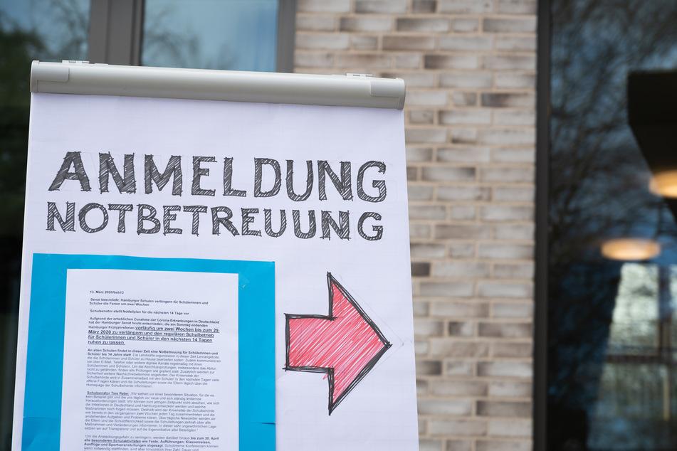 """Ein Flipchart mit der Aufschrift """"Anmeldung Notbetreuung"""" steht auf dem Gelände der Grundschule Hoheluft."""