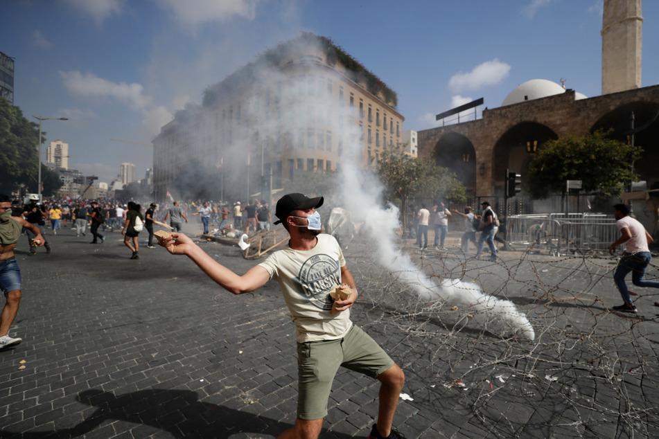 Ein Protestierender wirft Steine in Richtung der Sicherheitskräfte während eines Protests gegen die politischen Eliten und die Regierung nach der tödlichen Explosion im Hafen von Beirut.