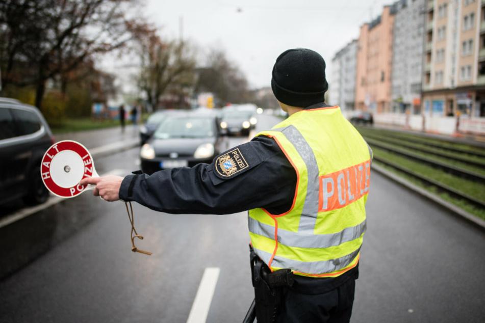 Ein Polizist stoppt an einer Kontrollstelle ein Fahrzeug mit seiner Kelle. Im Zuge der neu auferlegten Ausgangsbeschränkungen befragt die Polizei die Insassen von Fahrzeugen nach dem Grund und der Notwendigkeit ihrer Fahrt.