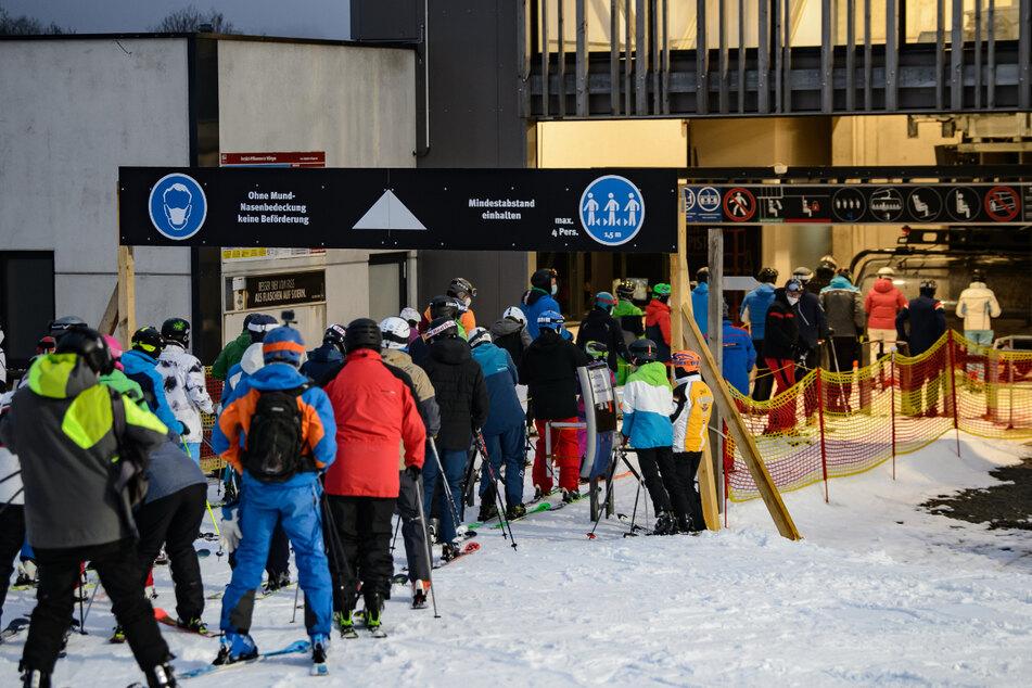 Wintersportler stehen beim Flutlichtskifahren an der Talstation Schlange.