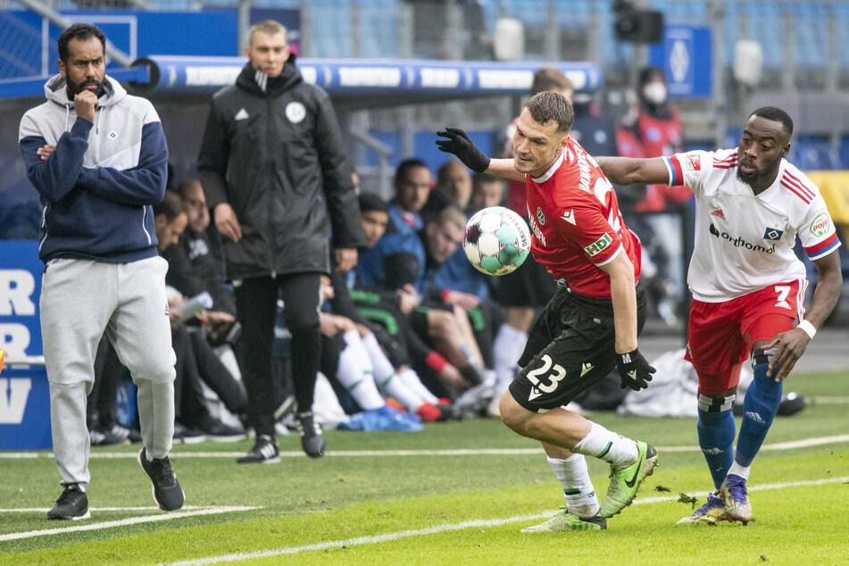 HSV-Trainer Daniel Thioune (l.) schaut zu, wie Hannovers Baris Basdas und Khaled Narey (r.) um den Ball kämpfen.