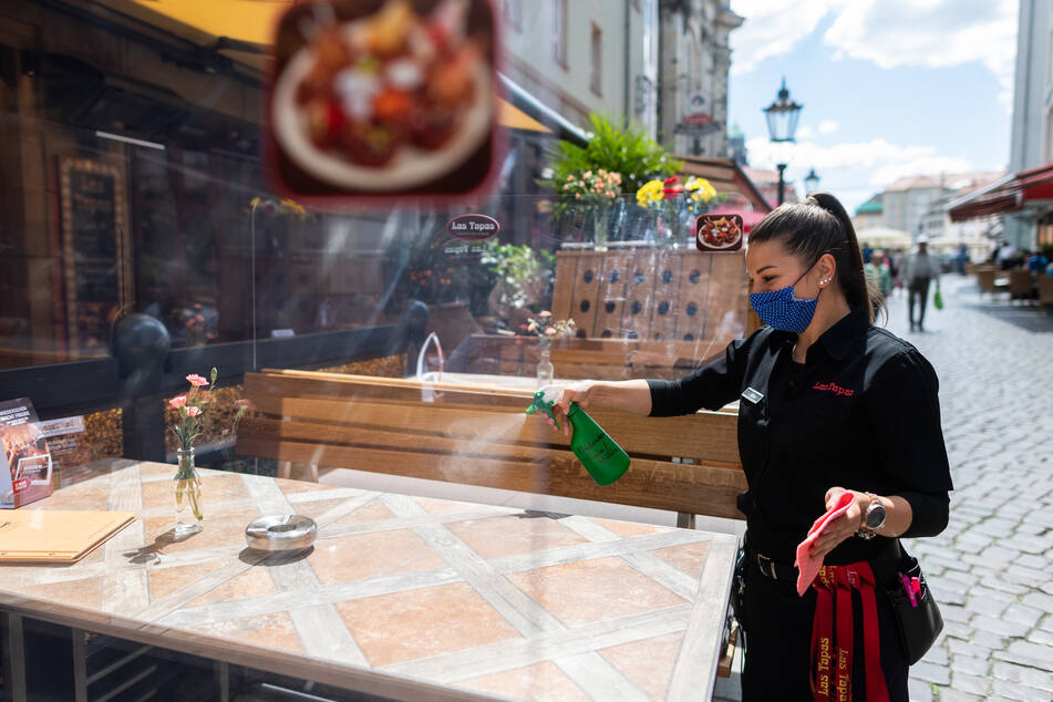 Eine Mitarbeiterin eines Restaurants in der Münzgasse reinigt die Tische, die mit Plexiglasscheiben getrennt sind, mit Desinfektionsmittel.