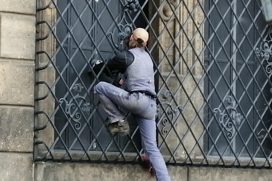 Ein Handwerker bearbeitet die frisch verschraubten Fensterläden am Historischen Grünen Gewölbe mit einer Schleifmaschine.