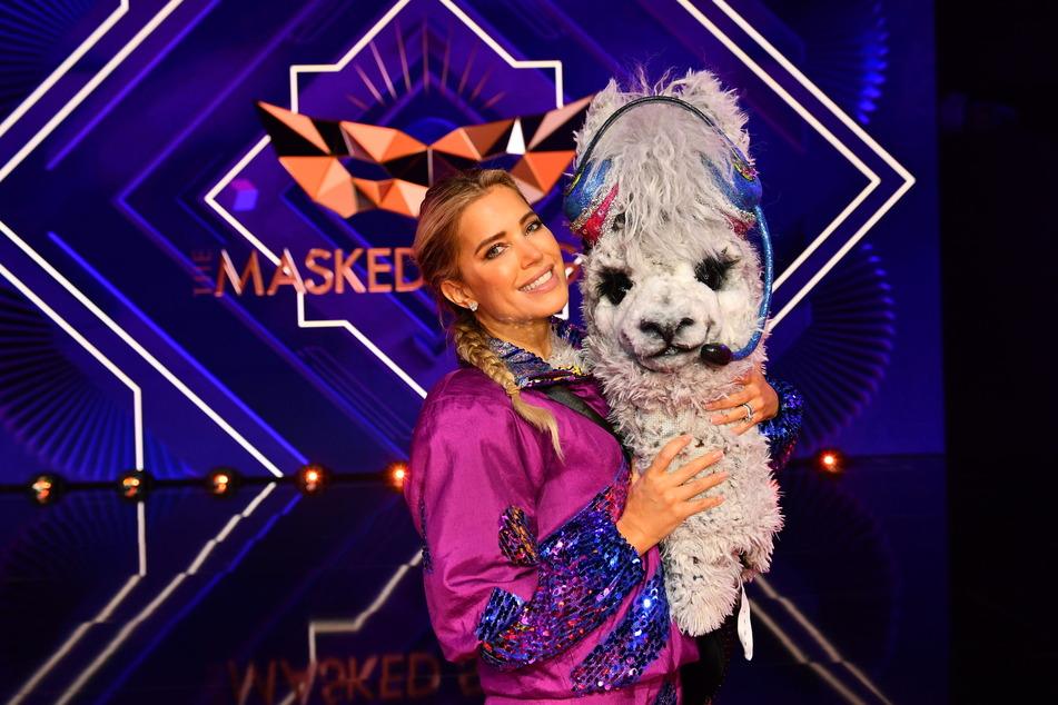 """Die Moderatorin hält die Maske der Figur des Alpakas bei """"The Masked Singer""""."""