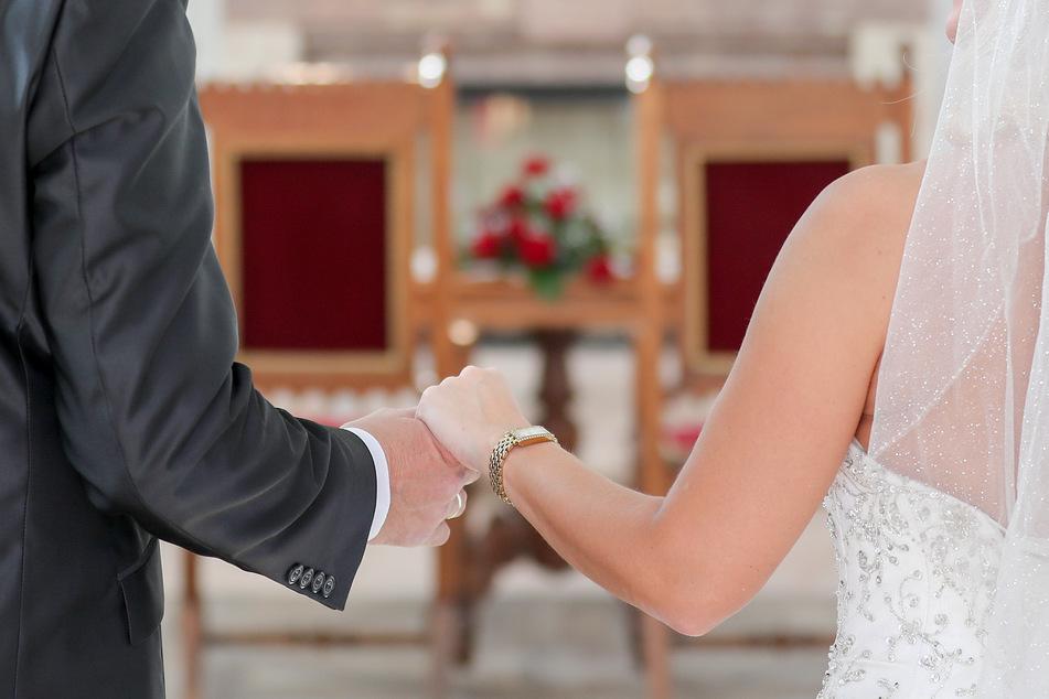 Ein Brautpaar steht in einer Hochzeitskapelle. Der Tanz zwischen den beiden ist nun wieder erlaubt.