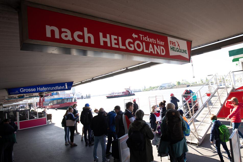 Fahrgäste stehen vor der High-Speed Fähre Halunder Jet an den Landungsbrücken.