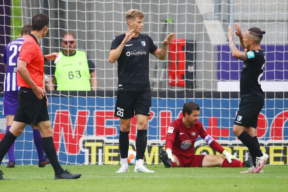 Luca Schuler (Mitte) und Baris Atik (rechts) klatschen nach einem Magdeburger Treffer ab. Aues Torhüter Martin Männel (am Boden) ist geschlagen.