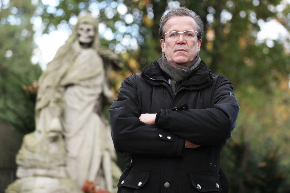 Christoph Kuckelkorn, Bestattungsunternehmer und Karnevalspräsident, steht auf dem Melatenfriedhof an einem Grab.