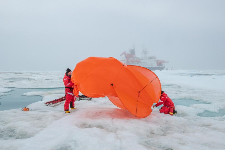 Mitarbeiter der Expedition packen einen Fesselballon zusammen.