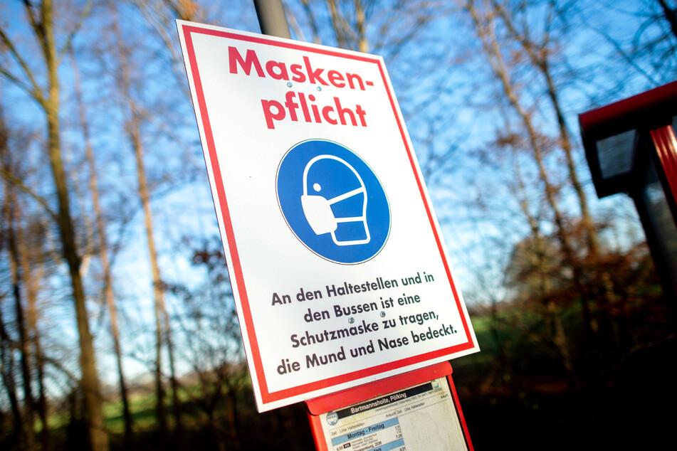 """Ein Schild mit der Aufschrift """"Maskenpflicht"""" hängt an einer Bushaltestelle. (Symbolbild)"""