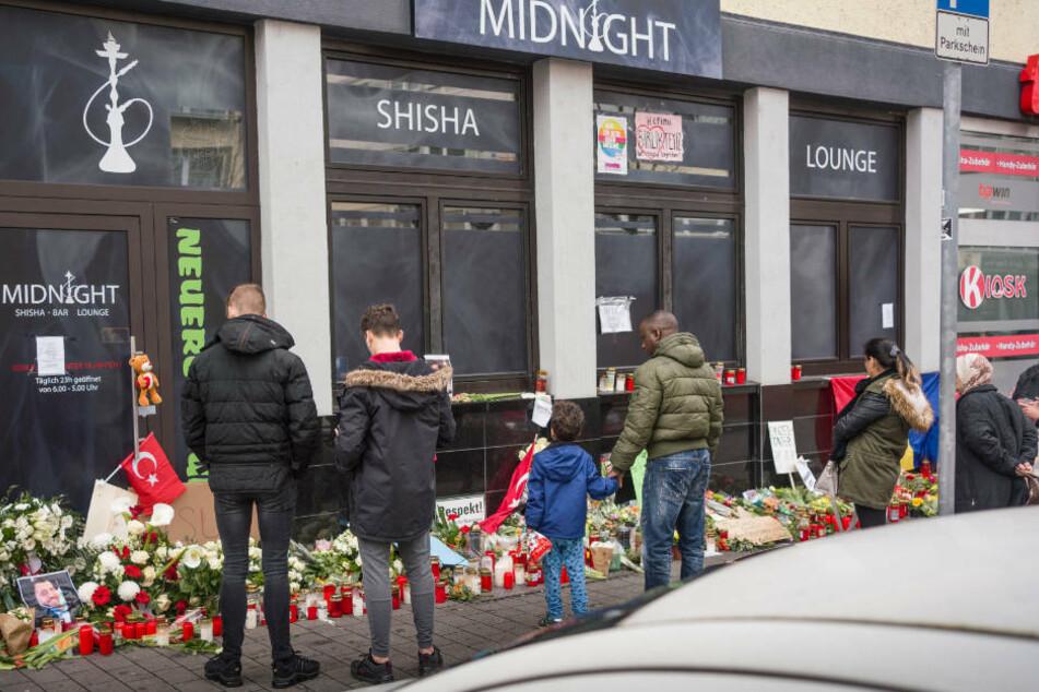 Menschen stehen eine Woche nach dem Anschlag an einem der Tatorte vor einer Shisha-Bar am Heumarkt in Hanau.