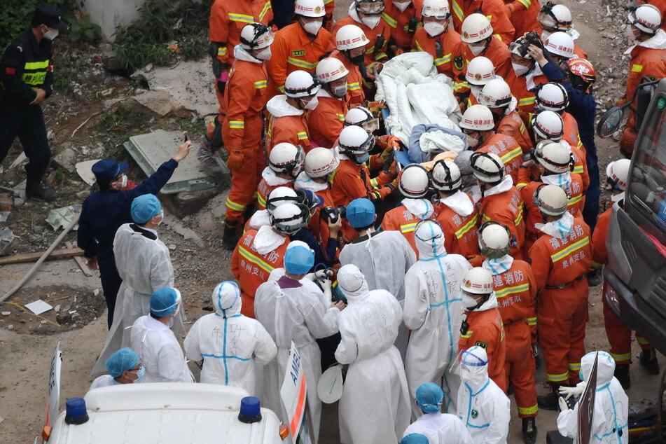 Einsatzkräfte bringen einen Mann, der aus den Trümmern eines eingestürzten Hotels geborgen werden konnte, zum Krankenwagen.