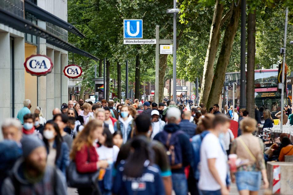 Menschen gehen auf einer Einkaufsstraße entlang.