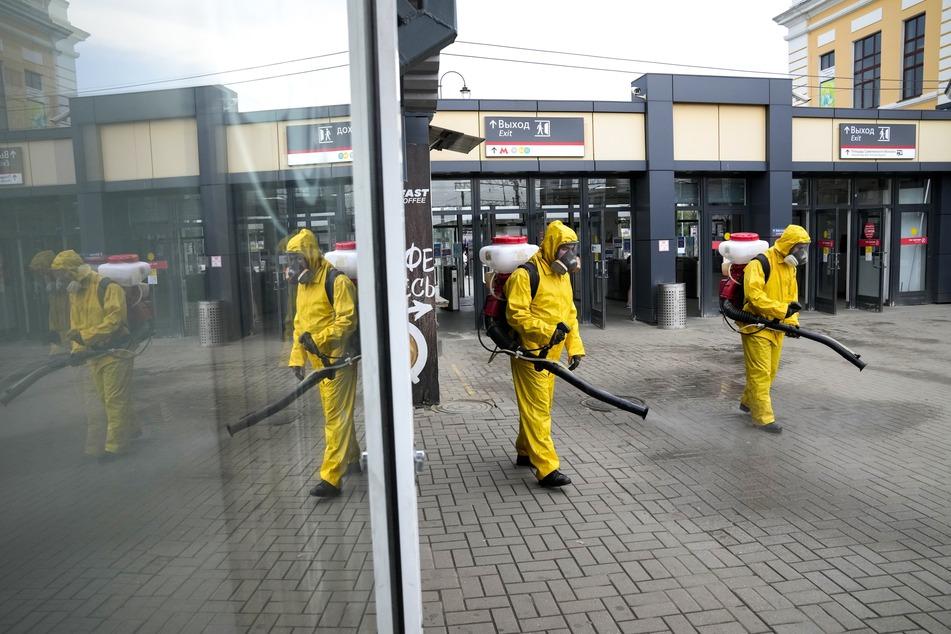 Mitarbeiter des Katastrophenschutzes desinfizieren einen Bahnsteig eines Moskauer Bahnhofs.